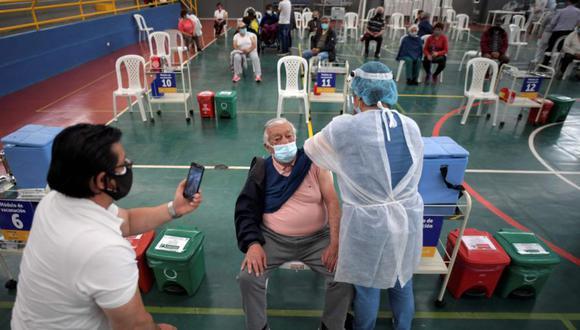 Un anciano es inoculado con la vacuna Oxford / AstraZeneca contra COVID-19 mientras un hombre le toma una foto, en medio de la pandemia del nuevo coronavirus, en Bogotá. (Foto: AFP / Raúl ARBOLEDA).