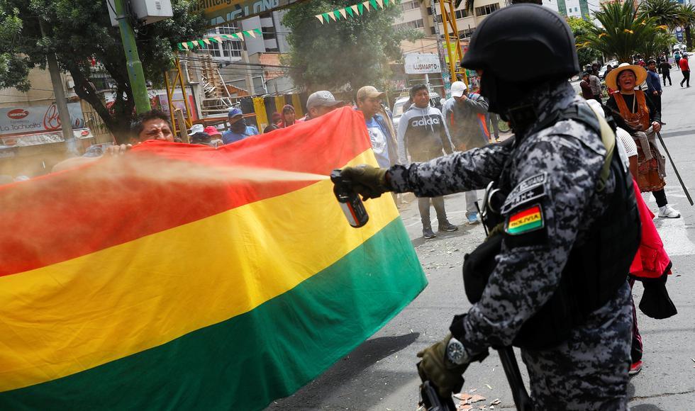Un miembro de las fuerzas de seguridad de Bolivia usa gas pimienta contra manifestantes que protestan en La Paz contra la reelección de Evo Morales. (REUTERS / Kai Pfaffenbach).