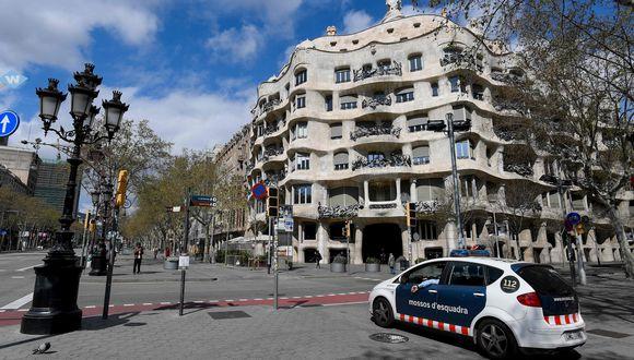 Un auto de la policía de Catauña delante de la Pedrera de Gaudí. Las calles se muestran vacías por el confinamiento del coronavirus. Foto: AFP