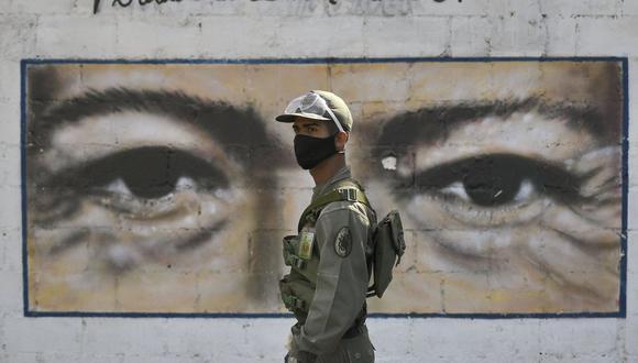 Un soldado vigila una mesa de votación en una escuela que tiene los ojos del fallecido presidente de Venezuela Hugo Chávez pintados en una pared durante las elecciones para elegir a los miembros de la Asamblea Nacional. (Foto AP / Matias Delacroix).