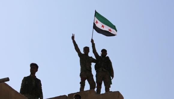 Combatientes sirios respaldados por Turquía agitan la bandera de la oposición siria en la cima de un edificio en la ciudad fronteriza de Tal Abyad. (AFP / Bakr ALKASEM).