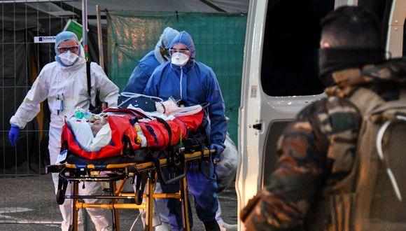 Emergency medical personnel carries a patient affected with coronavirus (Covid-19) from a military hospital to an ambulance before being transported aboard a medicalised TGV (high-speed train) to be evacuated towards hospitals of other French regions on March 29, 2020 in Mulhouse, eastern France, amid the spread of the COVID-19 (new coronavirus) pandemic. (Photo by SEBASTIEN BOZON / AFP)
