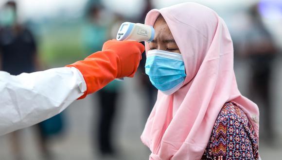 Un agente le toma la temperatura a una trabajadora migrante indonesia que acaba de llegar de Malasia antes de ingresar a un centro de cuarentena para prevenir el coronavirus. (EFE / EPA / DEDI SINUHAJI).
