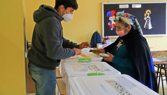 Una mujer indígena mapuche vota durante las elecciones para elegir alcaldes, concejales y una comisión para reescribir la Constitución de Chile en Temuco. (MARIO QUILODRAN / AFP).