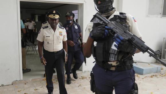 El director de la policía de Haití, Léon Charles, a la izquierda, se retira de un salón al término de una conferencia de prensa en la sede de la policía en Puerto Príncipe, el miércoles 14 de julio de 2021. (AP Foto/Fernando Llano).
