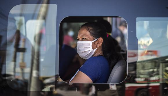 Una mujer usa una mascarilla en un bus de transporte público en Lima. (Foto: ERNESTO BENAVIDES / AFP)