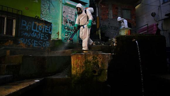 Un voluntario desinfecta un área dentro de la favela Santa Marta, en Río de Janeiro, Brasil, el 1 de agosto de 2020, durante la pandemia de coronavirus COVID-19. (Foto: CARL DE SOUZA / AFP).