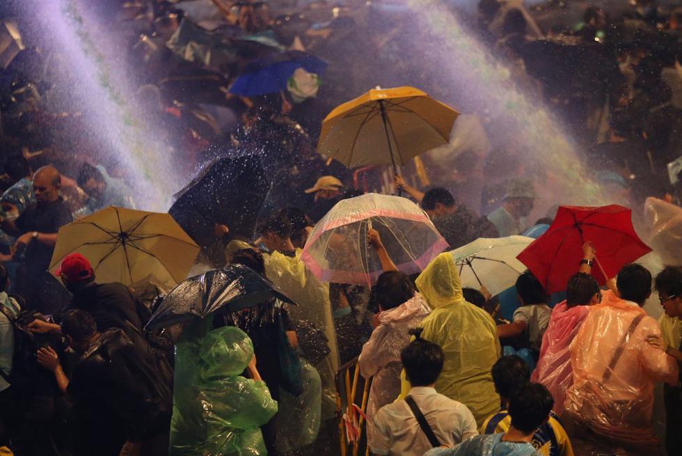 Ciudadanos a favor de la democracia reaccionan cuando la policía antidisturbios dispara cañones de agua durante una protesta en Bangkok, Tailandia. (EFE/EPA/NARONG SANGNAK).