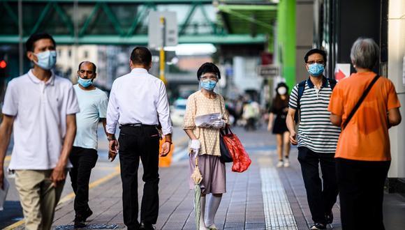 Los peatones usan máscaras faciales en el distrito Sham Shui Po, de Kowloon, en Hong Kong, a medida que entran en vigencia nuevas medidas de distanciamiento social que incluyen el uso de máscaras en público para combatir una nueva ola de coronavirus. (ANTHONY WALLACE / AFP)