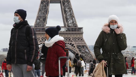 La gente camina cerca de la Torre Eiffel con máscaras protectoras en medio del brote de COVID-19, el nuevo coronavirus, en la explanada de Trocadero en París. (Foto: AFP)