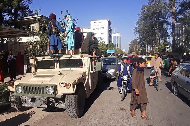 In this image taken on August 13, 2021, Taliban fighters stand in a military vehicle on the side of the road in Herat. (AFP).