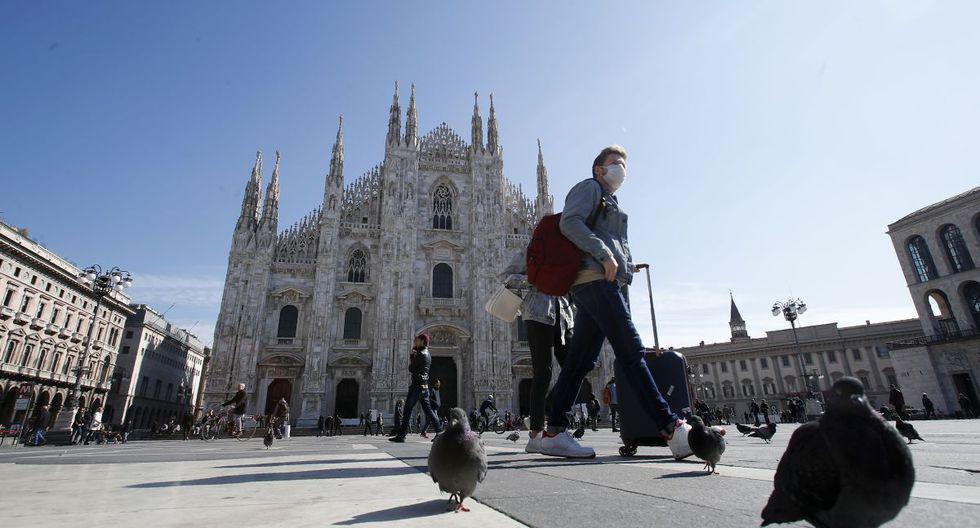 Esta foto de marzo muestra a un hombre con mascarilla caminando con su maleta frente a la catedral del Duomo, en el centro de Milán, Italia. (Foto: AP)