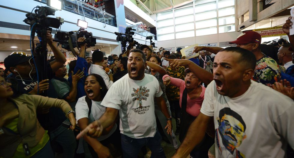 Los partidarios del gobierno de Nicolás Maduro gritan consignas contra los legisladores de la oposición que llegaron al aeropuerto de Caracas para recibir a Juan Guaidó. (Foto AP / Matias Delacroix)