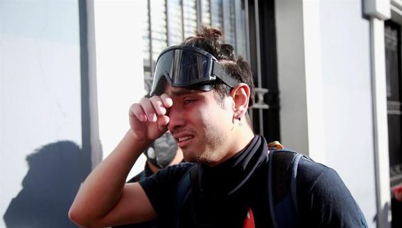 Un manifestante sufre los efectos de los gases lacrimógenos durante las protestas del domingo en Ciudad de Guatemala. (EFE/ Esteban Biba).