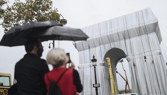 Dos personas miran cómo varios trabajadores envuelven en tela el monumento del Arco de Triunfo, el miércoles 15 de septiembre de 2021. (Foto: AP/Lewis Joly)