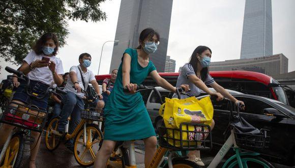 Las personas que usan máscaras faciales para protegerse contra el coronavirus esperan en una intersección en el distrito comercial central de Beijing. (Foto: AP / Mark Schiefelbein).