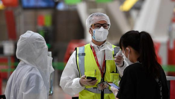 Un empleado con equipo de protección completo verifica la temperatura de los pasajeros que llegan para registrarse para su vuelo en el Aeropuerto de Madrid-Barajas Adolfo Suárez, el 20 de junio de 2020. (PIERRE-PHILIPPE MARCOU / AFP).