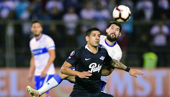 César Fuentes intentando quitarle la pelota a Luis Cardozo. (Foto: AFP)