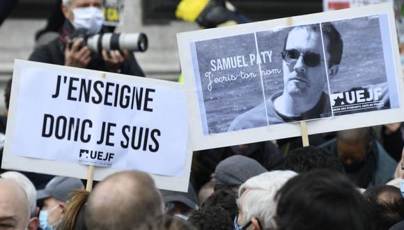 La gente sostiene un retrato del profesor de historia Samuel Paty mientras se reúnen en la Place de la République en París el 18 de octubre de 2020, dos días después de que fuera decapitado por un atacante. (Foto de Bertrand GUAY / AFP).