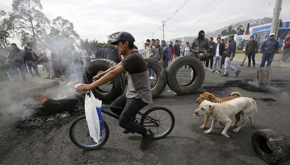 Un joven monta su bicicleta, mientras manifestantes cierran la carretera Panamericana durante una protesta contra la eliminación de los subsidios al combustible en Ecuador. (Foto: AP).