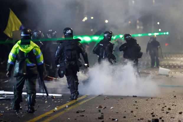 Integrantes del Escuadrón Móvil Antidisturbios (ESMAD) se enfrentan a manifestantes que llegan al barrio donde tiene su residencia el presidente de Colombia Iván Duque. (EFE/Mauricio Dueñas Castañeda).