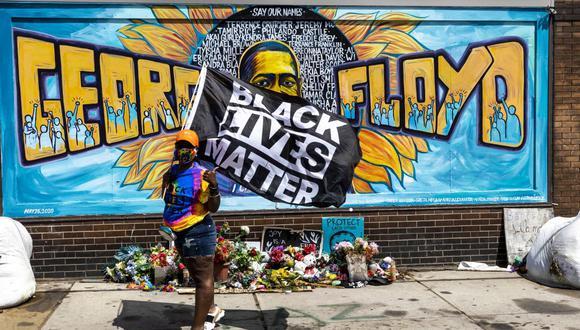Una mujer sostiene una bandera de Black Lives Matter frente a un mural de George Floyd en Minneapolis, Minnesota. (Foto: Kerem Yucel / AFP).