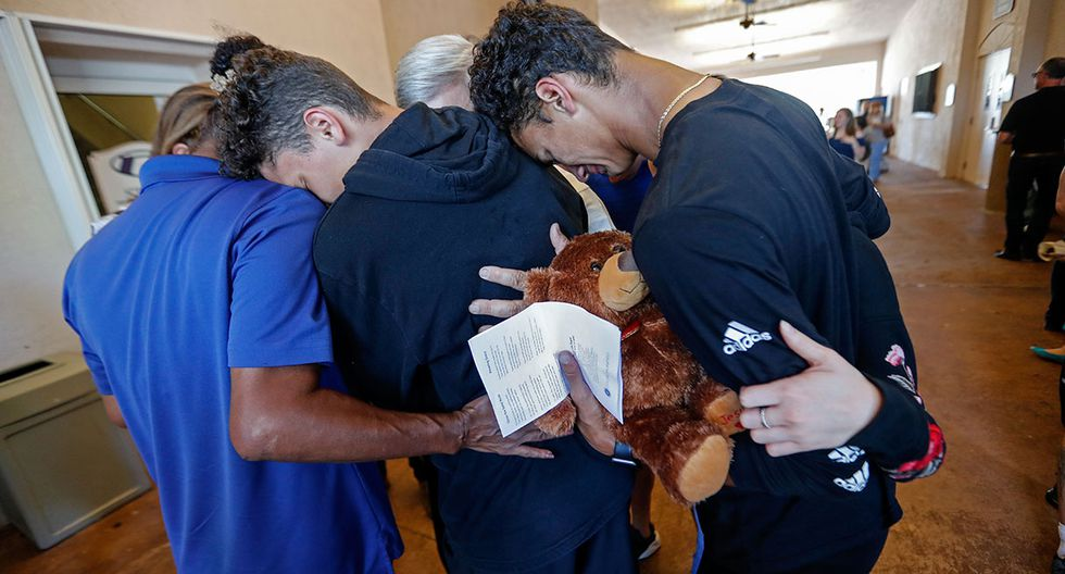 Students hug each other after a vigil at the Parkland Baptist Church, for the victims of the Wednesday shooting at Marjory Stoneman Douglas High School, in Parkland, Fla., Thursday, Feb. 15, 2018. Nikolas Cruz, a former student, was charged with 17 counts of premeditated murder on Thursday. (AP Photo/Gerald Herbert)