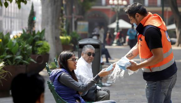 Un funcionario de Protección Civil reparte tapabocas este martes, en Puebla (México). (Foto: EFE)