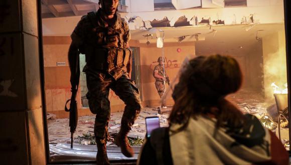Los manifestantes libaneses observan cómo los soldados custodian la sede de la Asociación de Bancos luego de que fuera asaltada e incendiada por manifestantes en el centro de Beirut. (Foto de ANWAR AMRO / AFP).