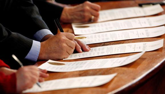 Representantes del Colegio Electoral de Carolina del Norte firman los Certificados de Voto en el edificio del Capitolio Estatal en Raleigh, Carolina del Norte, Estados Unidos. (Foto: REUTERS / Jonathan Drake / archivo).