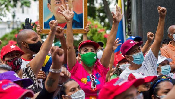 Simpatizantes del gobierno del presidente venezolano Nicolás Maduro celebran los resultados de las elecciones legislativas del 6 de diciembre con un retrato del fallecido presidente venezolano (1999-2013) Hugo Chávez en Caracas. (Foto: AFP / Cristian Hernandez).