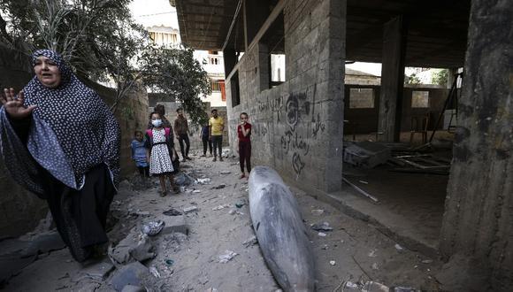 Una familia palestina rodea a una bomba que no explotó luego de ser arrojada por las fuerzas israelíes sobre su casa en el barrio de Rimal, en Gaza. La ONU calcula que unos 58 mil palestinos han sido desplazados durante la última escalada de violencia en la región. (Foto: Mahmud Hams / AFP)
