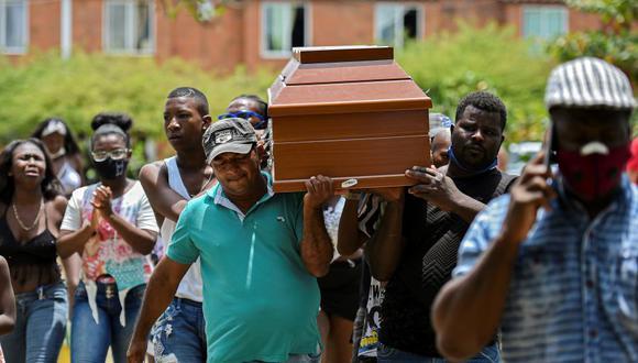 Amigos y familiares llevan el féretro de uno de los cinco jóvenes asesinados en un campo de caña de azúcar en Cali, Colombia, el 13 de agosto de 2020. (Foto de Luis ROBAYO / AFP).