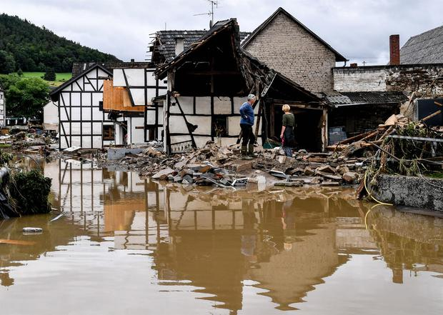 Locals inspect a house that collapsed after the July 15, 2021 flood from the Ahr River in Schultz, Germany.  (EFE / EPA / SASCHA STEINBACH).