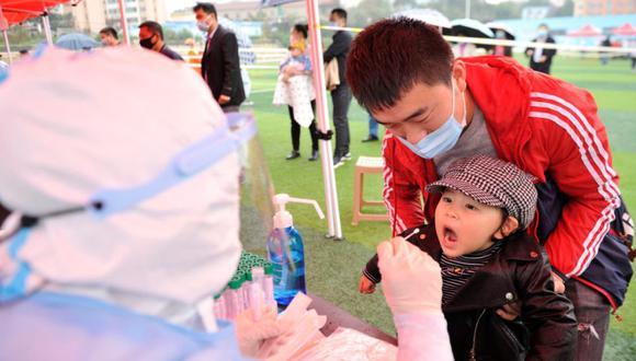 Un trabajador de la salud (izquierda) toma un hisopo de un residente para que se le haga la prueba del coronavirus COVID-19 como parte de un programa de pruebas masivas luego de un nuevo brote en Qingdao, en la provincia oriental de Shandong. (Foto: China OUT / AFP / STR).
