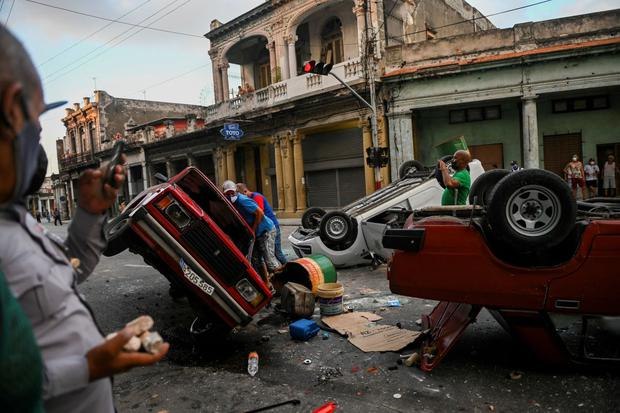 Cuban police cars overturned by protesters on Havana Street.  (YAMIL LAGE / AFP).