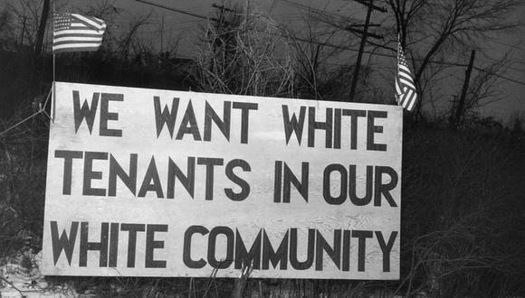 """Un aviso dispuesto en Detroit (Michigan) en 1942 frente a un proyecto de vivienda social que dice """"Queremos inquilinos blancos en nuestra comunidad blanca"""". (Getty Images)"""