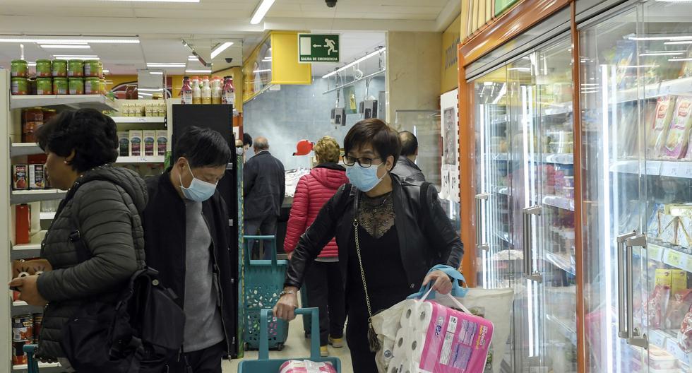 Las personas, algunas de ellas con máscaras protectoras a la luz del nuevo brote de coronavirus, hacen las compras en un supermercado en el barrio de Usera en Madrid. (AFP).