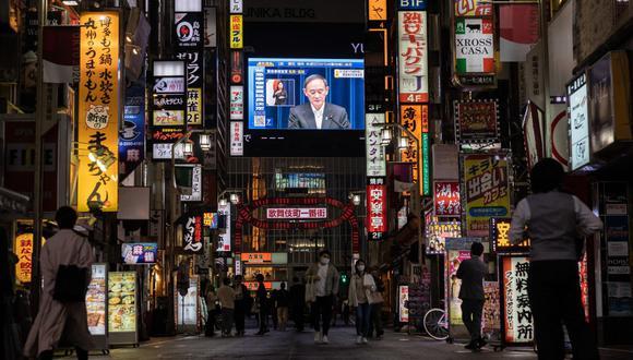 Una pantalla muestra al primer ministro japonés, Yoshihide Suga, hablando durante una conferencia de prensa para anunciar la extensión del estado de emergencia por coronavirus, en Tokio el 7 de mayo de 2021 (Foto: Yuki Iwamura/ AFP).