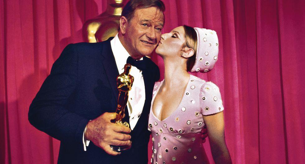 """John Wayne recibe el Óscar a Mejor Actor, en 1970, por su rol en """"Temple de acero"""". El anuncio lo hizo  una veinteañera Barbra Streisand. (Foto: Bettmann)"""