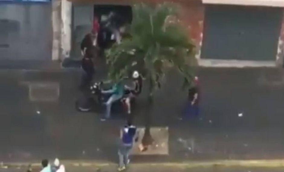 Venezuela: Vecinos evacuan en una moto a joven herida de bala. (Captura de video)