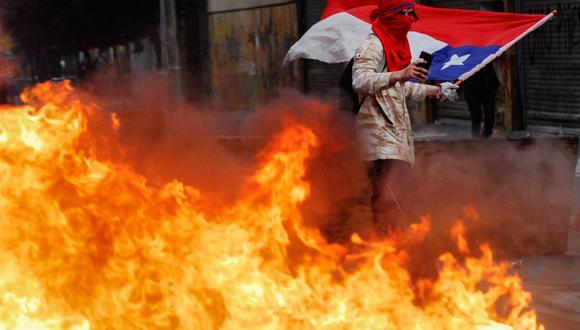 Un manifestante agita una bandera nacional chilena mientras está de pie detrás de un bloqueo en llamas durante las protestas contra el gobierno de Chile. La imagen es del 25 de octubre. (Foto: Reuters)