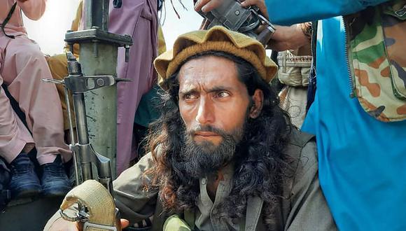 Un combatiente talibán se sienta junto a un vehículo en una calle de la provincia de Laghman, Afganistán, el 15 de agosto de 2021. (AFP).