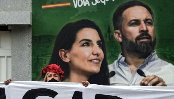 Una activista de Femen sostiene una pancarta frente a un cartel electoral que representa a los líderes del partido Vox, de extrema derecha, Rocío Monasterio y Santiago Abascal, durante una protesta en Madrid el 30 de abril de 2021, antes de las elecciones regionales. (Foto de OSCAR DEL POZO / AFP).
