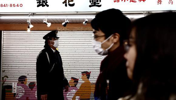 Un oficial de policía (izquierda) con una máscara facial para ayudar a prevenir la propagación del coronavirus camina por una calle en Tokio (Japón), el 2 de enero de 2021. (Behrouz MEHRI / AFP).