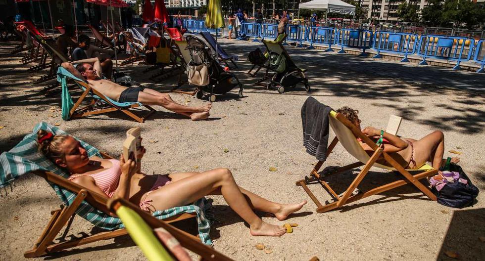 Las personas se sientan en sillas de playa al sol junto a una piscina temporal habilitada en el canal de Bassin de la Villette en París, Francia. (EFE/EPA/MOHAMMED BADRA).