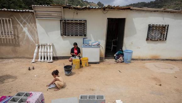 Una mujer lava ropa a mano al frente de su vivienda en el sector Las Piedras de San Isidro, en Caracas, Venezuela. (EFE/ Rayner Peña R.).