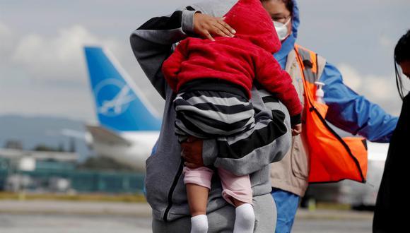 Una mujer carga a un niño a su llegada junto a un grupo de deportados desde Estados Unidos a la Ciudad de Guatemala. (EFE/ Esteban Biba).
