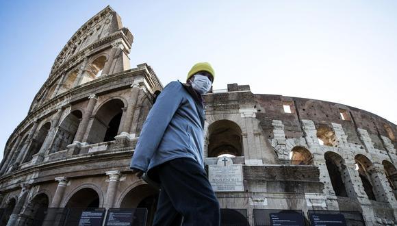 Un turista con mascarilla facial contra el coronavirus pasa cerca del Coliseo de Roma. (EFE/EPA/ANGELO CARCONI).