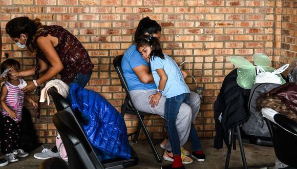 Una niña migrante de Centroamérica espera con su madre un autobús después de que la Oficina de Aduanas y Protección Fronteriza de Estados Unidos las dejara en una estación de autobuses cerca del Puente Internacional Gateway, entre las ciudades de Brownsville, Texas y Matamoros, México. (Foto de CHANDAN KHANNA / AFP).